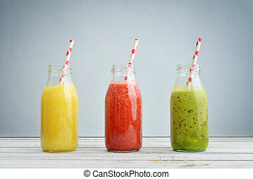 Fruit smoothies in retro bottles with drink straws on blue...