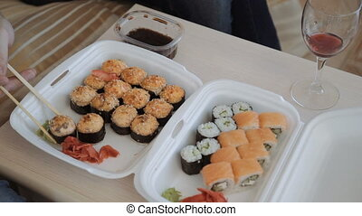 sushi from a lunchbox and drink red wine. close-up