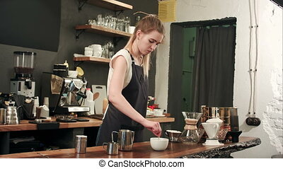 Pretty barista making coffee at cafe, pouring milk to a cup....