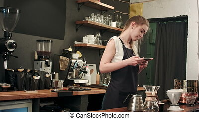 Female barista taking pictures of prepared cofee with...