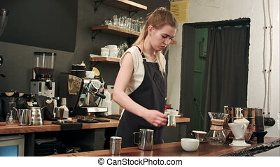 Barista pouring coffee and milk to a cup in the coffee shop
