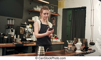 Cheerful female barista using smartphone to take selfie in...