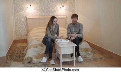 A young couple in a deluxe hotel room eat sushi from a...