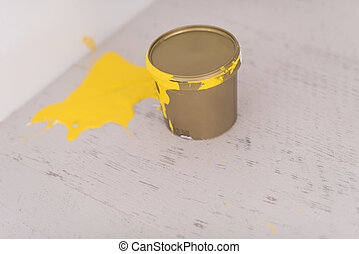Yellow paint tin can with yellow strokes on the wooden floor