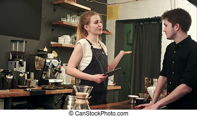 Female barista talking to customer in a cafe, taking order....