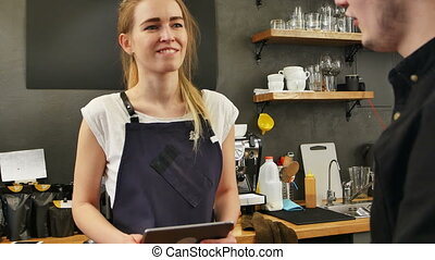 Portrait of a gorgeous female barista taking the order of a customer with a tablet computer and smiling