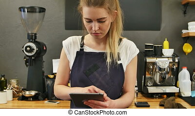 Smiling and cheerful barista using digital tablet for work....