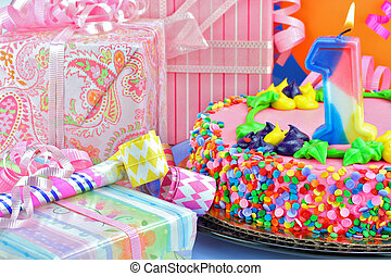 Feminine Birthday Cake with Lit Number One Candle surrounded by gifts.