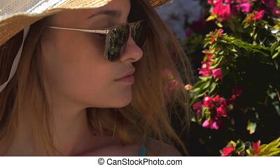 young girl with glasses stands near a flowering Bush in slow motion close-up