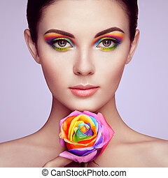 Portrait of beautiful young woman with rainbow rose