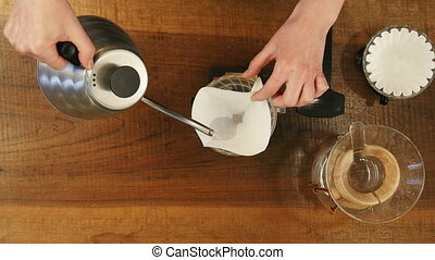 Barista pouring water on coffee ground with filter. Top...