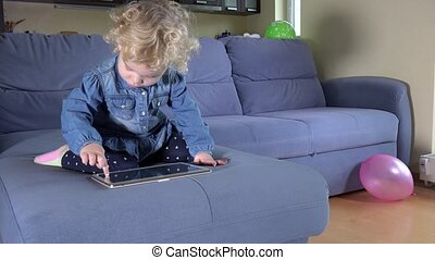 Little cute kid finger touch screen of tablet computer on sofa