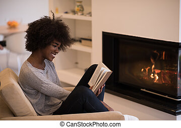 black woman at home reading book - Young beautiful african...