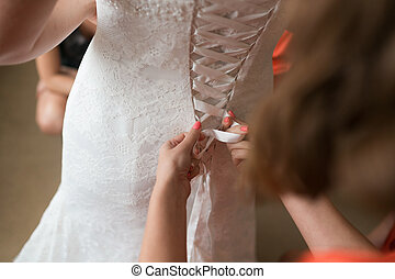 Bridesmaid dresses bride for the wedding day. Bridesmaid helps with a white dress before the ceremony. Luxury bridal dress close up. Best wed morning. concept