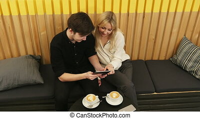 Young couple looking at tablet and drinking coffee. Top...