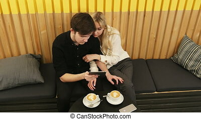 Cheerful couple sitting at coffee shop and websurfing on...