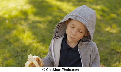 A cute boy eating a banana - A child is eating a banana on a...