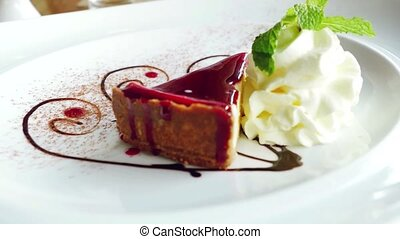 Delicious slice of Cheesecake beautiful served on a white plate with cream and leaf of mint.