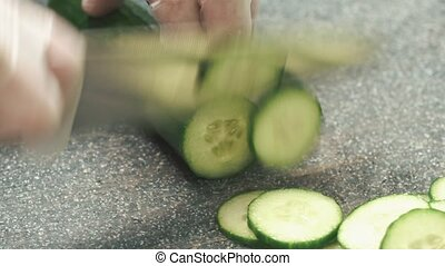 The hands of young man cook cut thin slices of green organic cucumber with knife on cutting Board, close up