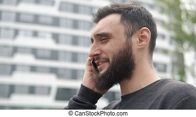 young man with beard talking on the phone near high-rises
