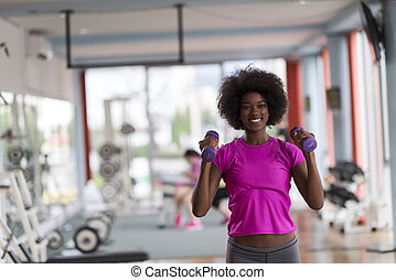woman working out in a crossfit gym with dumbbells - happy...