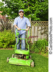 Man mowing lawn - Man with lawn mower in landscaped backyard