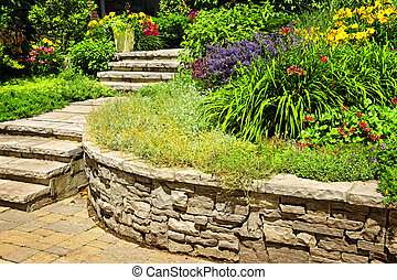 Natural stone landscaping in home garden with stairs and...