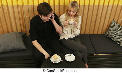 Young man calling by mobile phone, while sitting in cafe with girlfriend