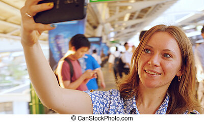 Cheerful woman taking selfie with smartphone in busy train...