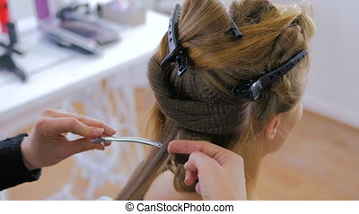 Professional hairdresser doing hairstyle for pretty woman -...