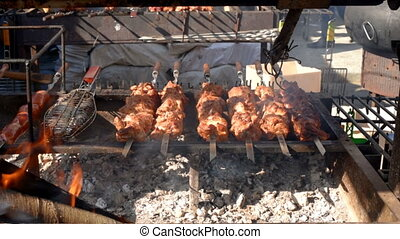 Grilled meat on skewers. Street food. Meat rotating on...