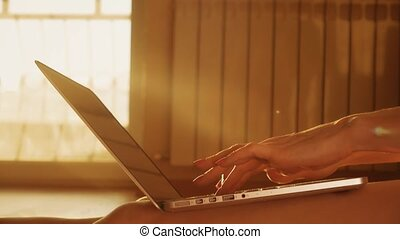 Beautiful female hands typing on a laptop keyboard.