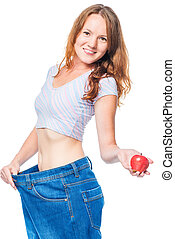 Beautiful smiling girl with an apple in her hand and big jeans on a white background
