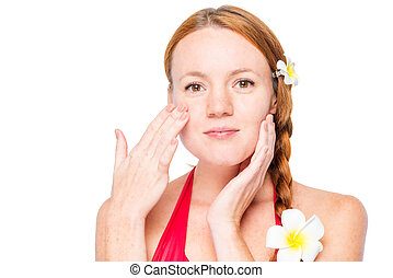 Woman's face with frangipani in her hair touches her skin on a white background
