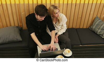 Detached couple using laptop computer in coffee shop. Top...