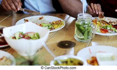 people eating food at restaurant table - leisure, food and...
