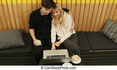Attractive young couple using a laptop computer to watch their favorite TV show at cafe