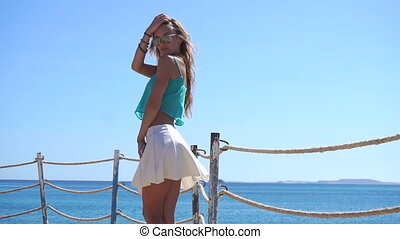 sexy young girl in glasses stands near the sea keeps your...