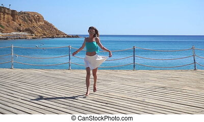 girl with long hair and glasses runs on pier near blue sea in slow motion