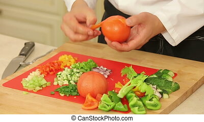 Peeling blanched tomatoes - Chef is peeling blanched...