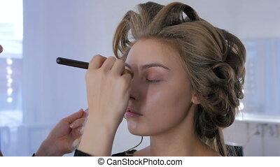 4 shots. Makeup artist applying liquid tonal foundation on...