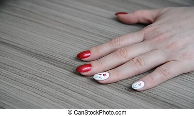 woman covers her fingernails with her colorless varnish over...
