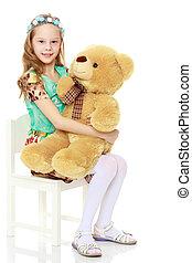 Girl holding a large Teddy bear.