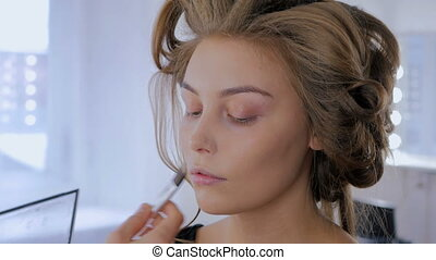 Professional make-up artist applying makeup on woman's face....