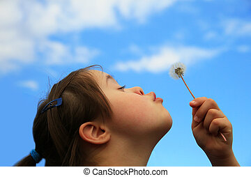 Down syndrome girl blowing dandelion