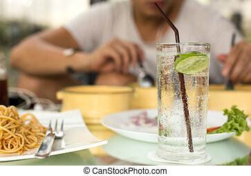 Man having glass of fresh sparkling mineral water with his...