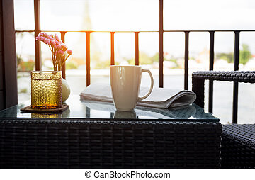 Conceptual Cup of coffee with glass water and newspaper on...