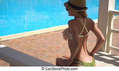 sexy girl sitting poolside in a hat and corrects swimsuit