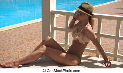 beautiful girl in a bathing suit hat and glasses sitting on...