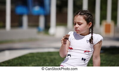 Cute girl eating brown ice cream in the park in the summer...